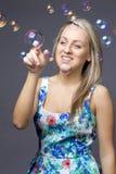 有肥皂泡的女孩金发碧眼的女人在白色 免版税库存图片