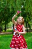 有肥皂泡的美丽的礼服女孩 免版税库存照片