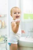 有肥皂的孩子洗涤的手在卫生间里 免版税库存图片