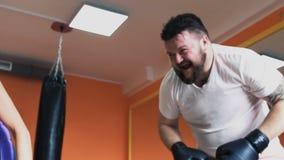 有肥胖人傻瓜的一个亭亭玉立的女孩和获得在健身房的乐趣 妇女打拳击手套的一个肥满冒汗的人 单独重量 股票视频