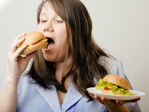 有肥胖的白人妇女在汉堡包之间的选择 图库摄影