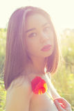 有肥满嘴唇的美丽的性感的女孩有鸦片花的在手上有在日落的露出的肩膀的在一个领域在阳光下 库存图片