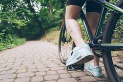 有肮脏的妇女腿从链子的油在自行车 库存照片