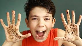 有肮脏的手微笑的恶作剧青少年的男孩 库存照片