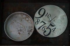 有肮脏的拨号盘的灰色圆的时钟和不对称在一个圆的灰色碗旁边的被安排的黑数字在黑背景 免版税库存图片