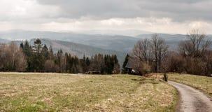 有肮脏的路、房子和小山的草甸在Beskids山的背景 免版税库存图片