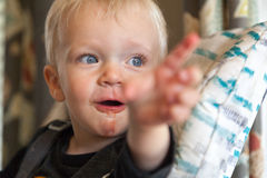 有肮脏面孔指向的好奇男孩 免版税库存图片