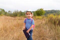 有背包和书的一个小女孩 库存照片