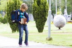 有背包和书的男孩在他的手上 室外 库存图片
