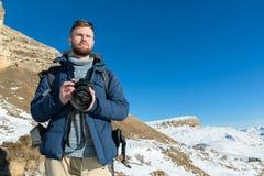 有背包和佩带的太阳镜的画象A有胡子的行家摄影师在他的手上站立与一台DSLR照相机 图库摄影
