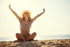 有背包和帽子的愉快的旅游女孩在海 免版税库存图片