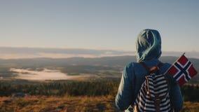 有背包和挪威旗子的一名妇女沿美丽如画的山行迹走在挪威 旅行 股票录像