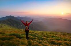 有背包和棍子的红发女孩运动员在绿色小丘站立并且看高山风景 库存照片