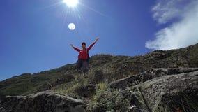 有背包和盖帽的年轻愉快的torist妇女在天空中到达了山上面并且投入了他的手 正面图 股票视频