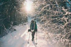有背包和雪靴的妇女在冬天山 免版税库存图片