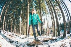有背包和雪靴的妇女在冬天山 免版税库存照片