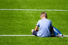 有背包坐的体育场的哀伤的单独男孩户外 库存照片