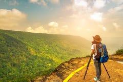 有背包帽子的在三脚架的妇女和照相机在山峭壁的上面站立观看美丽的景色的年轻旅行的 免版税库存图片
