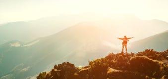 有背包微小的小雕象的高山徒步旅行者在山峰站立 免版税库存照片