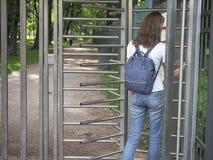 有背包旋转门的夫人在一个私有公园 库存照片