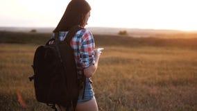有背包查寻位置航海的行家远足者剪影女孩走的流浪汉在手机智能手机 股票录像