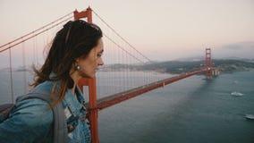 有背包步行的侧视图年轻美丽的旅游妇女观看日落有风金门大桥的庄严风景  影视素材