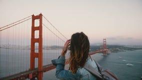 有背包步行的年轻女性创造性的工作者观看史诗风景,在强风的著名日落金门大桥的 股票录像
