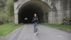 有背包步行的旅客妇女单独在道路隧道在路 股票录像