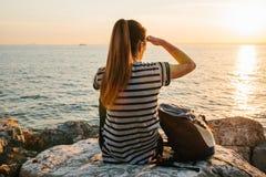 有背包的一个年轻旅游女孩坐岩石在海旁边在日落并且调查距离 其它 库存照片