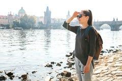 有背包的一个美丽的年轻旅游女孩在河伏尔塔瓦河旁边站立在布拉格并且敬佩建筑学  图库摄影