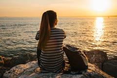有背包的一个年轻旅游女孩坐岩石在海旁边在日落并且调查距离 其它 图库摄影