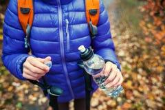 有背包的一名妇女打开一个瓶水 免版税库存图片