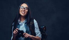 有背包的一名妇女拿着紧凑照片照相机 免版税库存图片