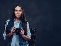 有背包的一名妇女拿着紧凑照片照相机 免版税库存照片