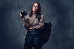 有背包的一名妇女拿着紧凑照片照相机 图库摄影