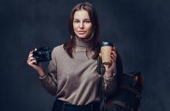 有背包的一名妇女拿着紧凑照片照相机 免版税图库摄影