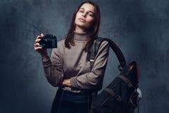有背包的一名妇女拿着紧凑照片照相机 库存图片