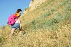 有背包的一名妇女攀登小山 库存图片