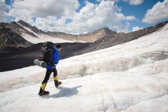 有背包的一名登山家在起重吊钩走走沿与边路的多灰尘的冰川的在手上在镇压之间 免版税库存图片