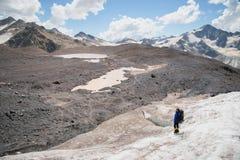有背包的一名登山家在起重吊钩走走沿与边路的多灰尘的冰川的在手上在镇压之间 免版税图库摄影