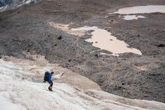 有背包的一名登山家在起重吊钩走走沿与边路的多灰尘的冰川的在手上在镇压之间 库存照片