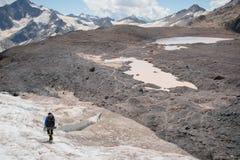 有背包的一名登山家在起重吊钩走走沿与边路的多灰尘的冰川的在手上在镇压之间 图库摄影