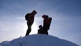 有背包的三个游人在冬天攀登了在明亮的太阳的光芒的小山 登山人在多雪顶部 股票视频