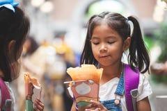 有背包的两个亚裔儿童女孩一起吃薄煎饼的在学校以后在学校 图库摄影