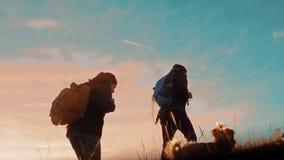 有背包的两个游人徒步旅行者人在日落去远足旅行 徒步旅行者冒险,并且狗去走 旅行 影视素材