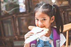 有背包的亚裔儿童女孩吃薄煎饼的在学校以后在学校 免版税库存照片