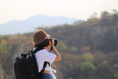 有背包的亚裔女孩旅客享用与藏品DSLR照相机在他的手上和站立在山背景,旅行的 库存照片