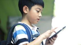 有背包的亚裔孩子使用一个数字式手机 影视素材