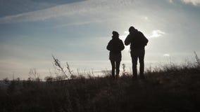 有背包的享受从山的上面的两个远足者剪影日落视图 享受日落视图从 影视素材