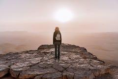 有背包的单独女孩在以色列Neqev沙漠敬佩日出看法  年轻女性在边缘站立 库存照片